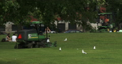 Small tractor cutting grass in a parc in Montreal Stock Footage