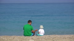 Father and son game, throw stones, turquoise sea water, having fun at seaside 4K Stock Footage