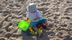 Little boy play with bucket, shovel, colored toys in the shore sand on beach 4K Stock Footage