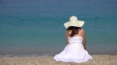 Single woman sitting on beach sand, admiring turquoise sea waves splashing 4K Stock Footage