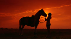Silhouettes of woman and her horse at sunset in the field - stock footage