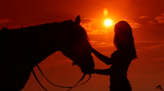 Silhouette of young girl rider with horse against sun and dramatic sky Stock Footage