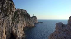 Rocky seashore, lighthouse on the cliff coast sea waving 4K Stock Footage