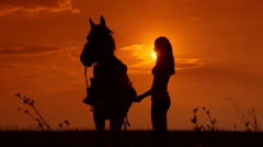 Female rider riding horse to horizon at sunset - stock footage