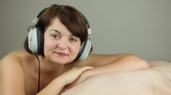 Stock Video Footage of Topless young adult woman with retro headphones blows a kiss