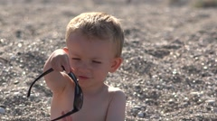 Funny child arrange sunglasses and waving hands, seashore sand - stock footage
