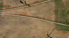 High Overhead Angle of Distant Men Crossing Path in Empty Field Stock Footage