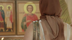 Christian woman praying before icon in Orthodox Church Stock Footage