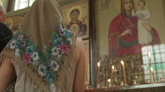 Mother with child praying before icon in Orthodox Church Stock Footage