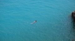 Man swimming alone in large turquoise sea water, feeling free Stock Footage