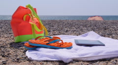 Beach bag flip flops towel and tablet computer at summer shore Stock Footage