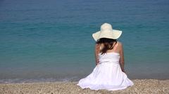 Single woman sitting on beach sand, admiring turquoise sea waves splashing Stock Footage