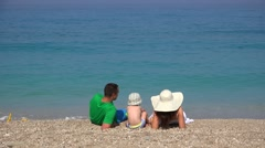 Stock Video Footage of Family relaxing on the beach, turquoise water, enjoying summer