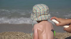 Mother hand spray on child with sun protection lotion, waves splashing Stock Footage