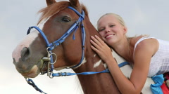 Face happy girl rider sitting in the saddle on a horse Stock Footage