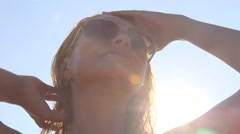 Young girl wearing aviator sunglasses after swimming in sunshine at the beach Stock Footage