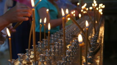 Faithful people lighting prayer candles in the church close-up - stock footage