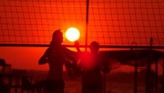 Young people group have fun and play beach volleyball at sunset Stock Footage