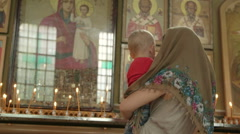 Mother with child lighting prayer candle in Christian Orthodox Church - stock footage