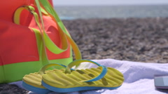 Colorful bag flipflops and towel at summer beach Stock Footage