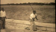 1150 - casting a heavy rod from ocean side dock - vintage film home movie Stock Footage