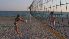 Young couple spend a weekend playing beach volleyball Stock Footage