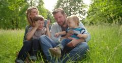 Family In Park playing Peekaboo Stock Footage