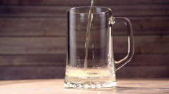 Beer is pouring into glass and foam hat Stock Footage