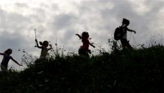 Silhouette of children. Kids running on right over the hill. Teens. Cloudy sky. - stock footage