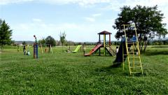 Children playing on the playground. Swing, seesaw, slide. Kids game in the park. - stock footage