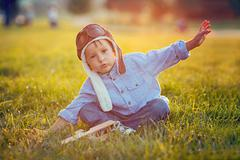 cute boy, playing with airplane on sunset in the park - stock photo