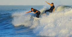 4K UHD. Surfers surfing hurricane Marie waves at sunset. Collision accident. - stock footage