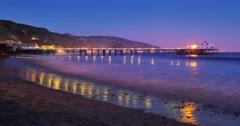 Illuminated pier and ocean waves night beach. Maliby, California. 4K Timelapse Stock Footage