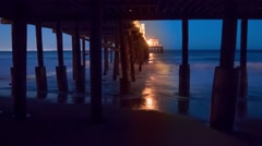 Ocean waves rolling under Malibu Pier at night. 4K UHD timelapse. - stock footage