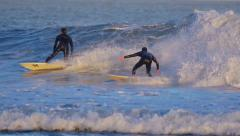 Surfers surfing hurricane Marie waves at sunset. Slow motion. - stock footage