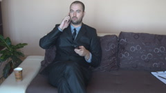Business man lying on couch, mobile phone talk remote controller in hand, coffee Stock Footage