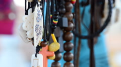 Hippies and tribal necklaces hanging in stall hawking crafts Stock Footage