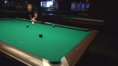 Night club with pool tables, man having fun play billiards, great shot in pocket Stock Footage