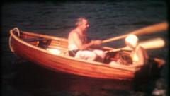 1160 - couple row off in a classic wooden rowboat - vintage film home movie - stock footage