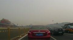 Cars drive past Tiananmen Gate on Chang'an Avenue amid the heavy haze - stock footage