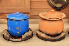 Clay pot and zinc on stove. Stock Photos