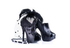 Black high heel shoes, bead necklace, and feather hair fascinator Stock Photos