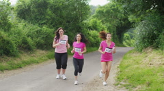 Happy group of female friends taking a break during charity fitness event Stock Footage