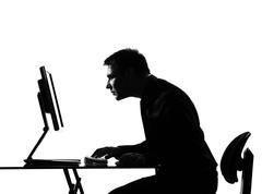 Silhouette  man  computing staring at the monir Stock Photos