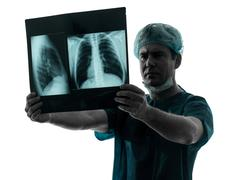 Doctor surgeon radiologist examining lung torso  x-ray image silhouette Stock Photos