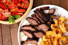 flank steak with fries onion rings and salad - stock photo