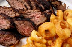 flank steak with fries onion rings - stock photo