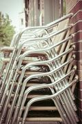 A stack of aluminum chairs from a restaurant Stock Photos
