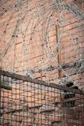barb wire with red brick wall in background - stock photo