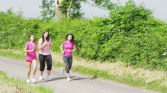 Female friends in pink t shirts, running together outdoors in the countryside - stock footage